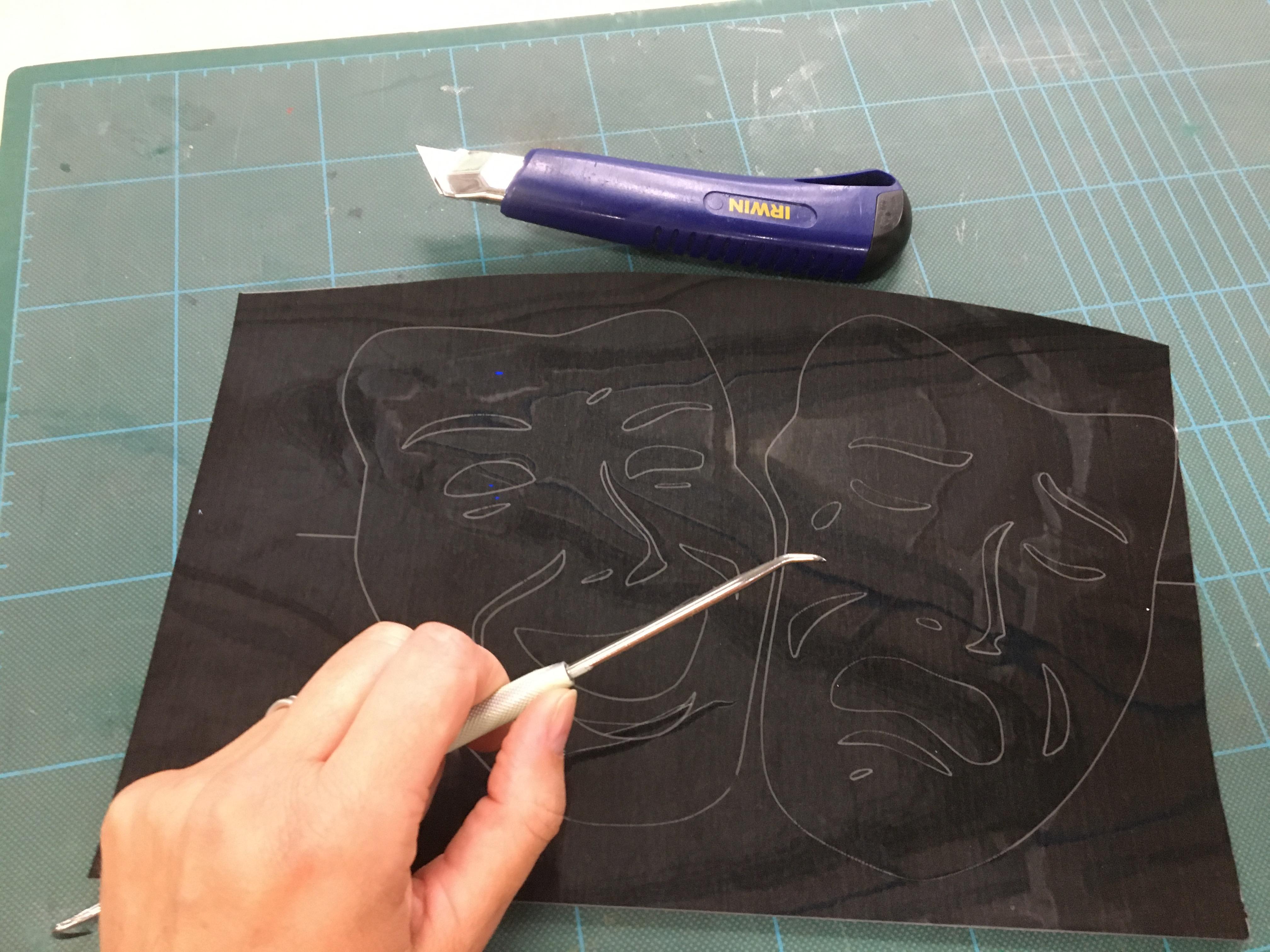 Elev er ved at fjerne omkransende foliestykker på et stykke sort folie hvori der er udskåret en glad og en sur maske.