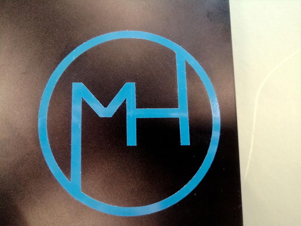 MH tegnet ind i en cirkel og skåret ud med laserskærer.