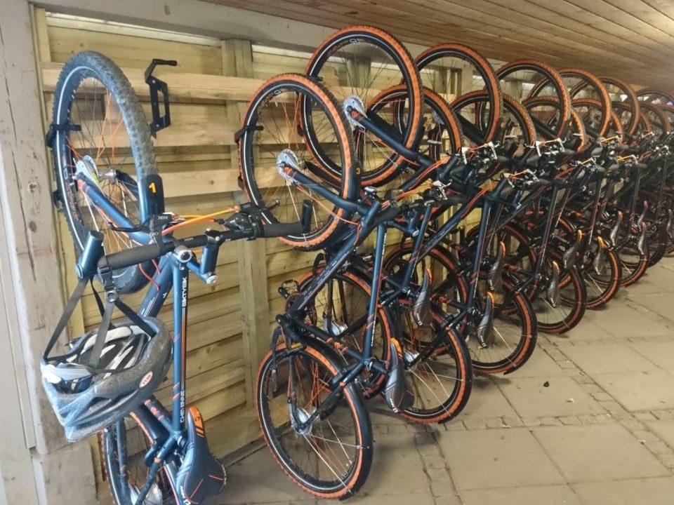 Cykler hænger på rad og række i cykelskur