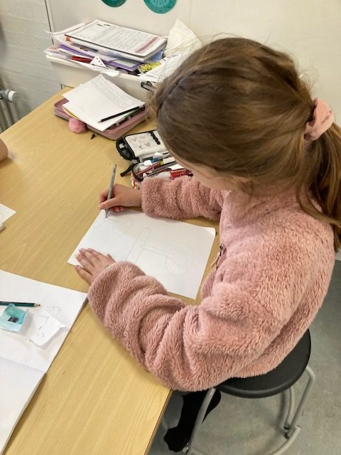 Pige sidder ved vord og tegner sine idéer ned