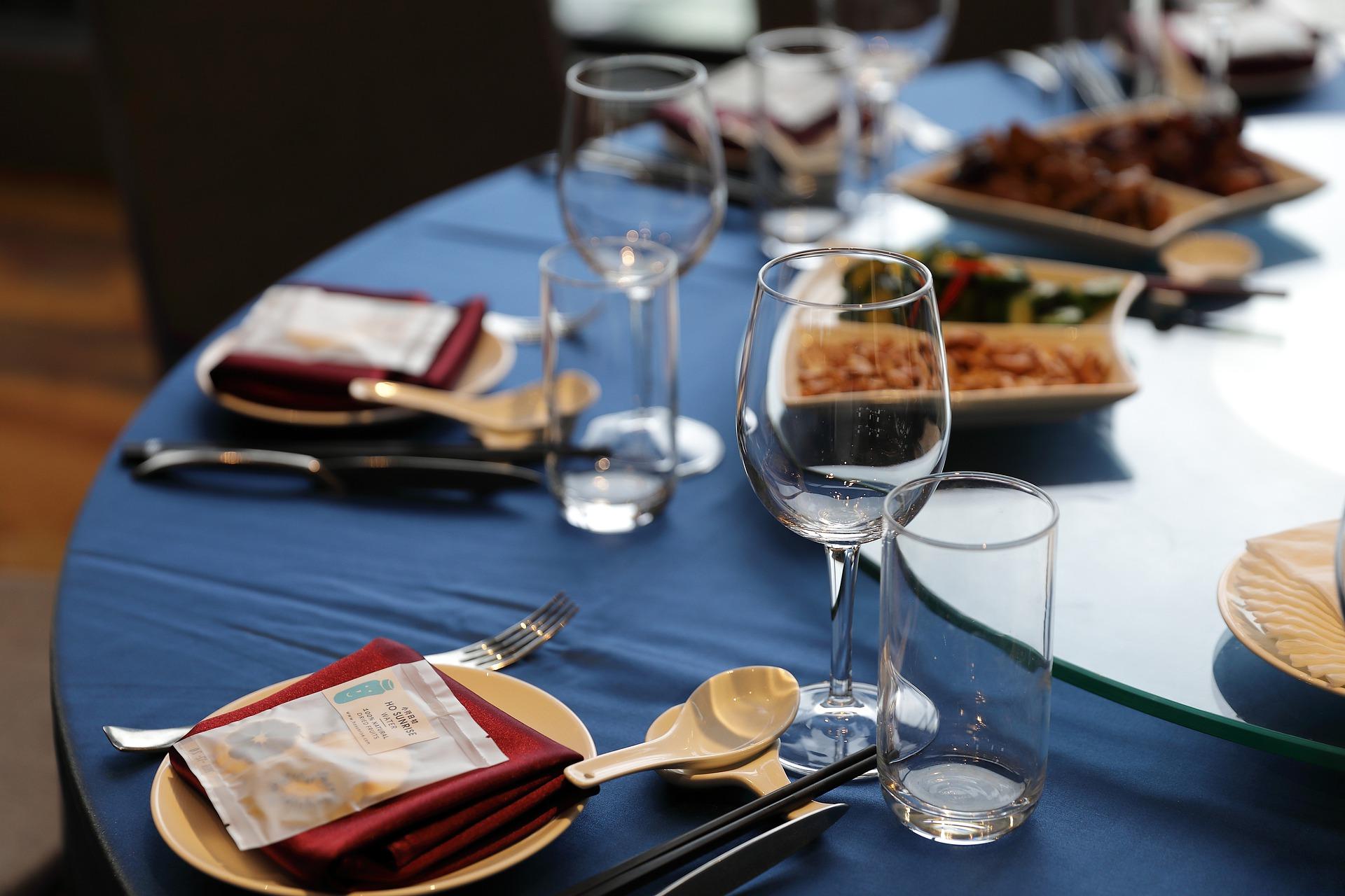 Dækket bord med blå dug, service, vinglas og bordpynt