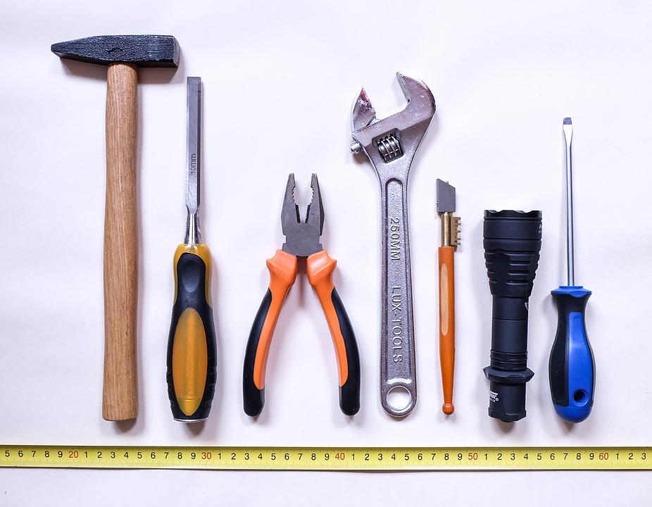 Værktøj på en række: Hammer, skruetrækker, tænger og kniv