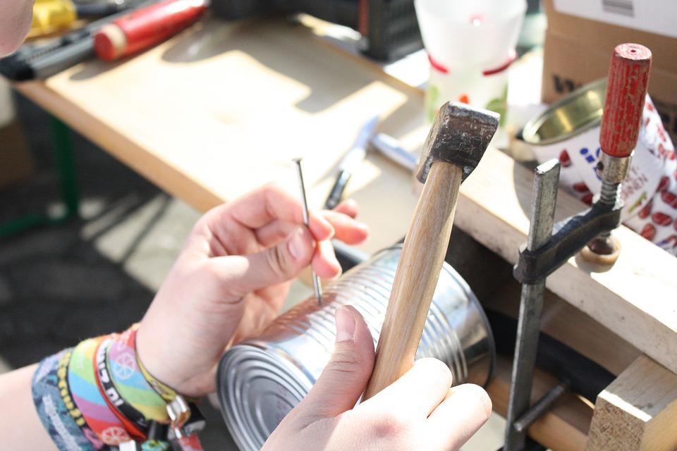 Barn hammer et søm i en metal dåse.