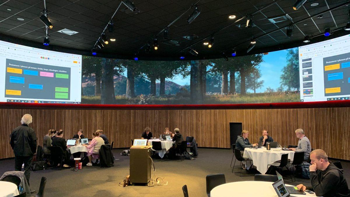 Der arbejdes ved gruppeborde i AI Innovation House i Vejle. Lokalet er rundt og har en stor skærm hele vejen rundt under loftet